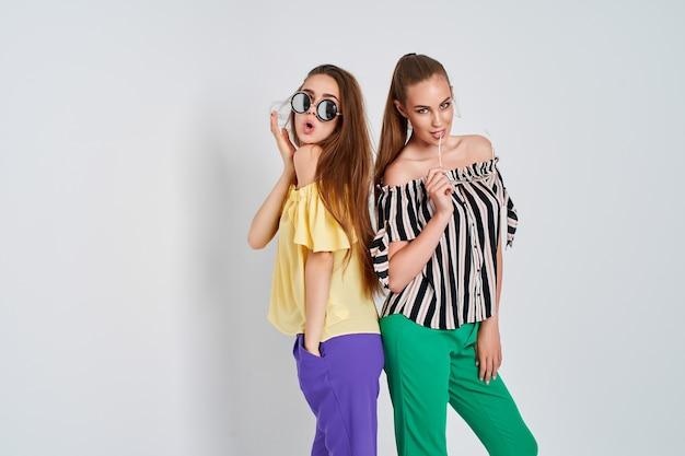 Duas mulheres jovens em roupas elegantes, moda, estúdio de beleza, tiro em fundo branco Foto Premium