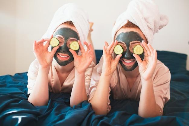Duas mulheres jovens em toalhas e pijamas têm uma divertida festa no spa juntos em casa.
