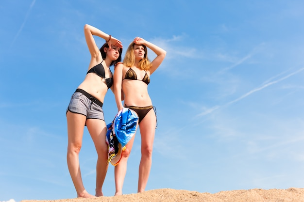 Duas mulheres jovens em trajes de banho na praia, procurando alguém à distância
