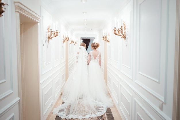 Duas mulheres jovens em vestidos de noiva andam por um longo corredor branco