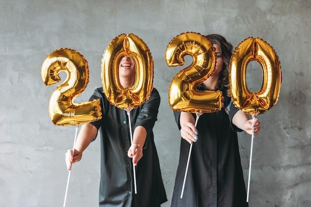 Duas mulheres jovens em vestidos pretos, segurando os balões de números 2020 no fundo da parede cinza