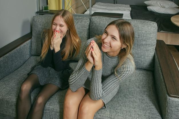 Duas mulheres jovens esbeltas de etnia caucasiana estão rindo enquanto estão sentadas no sofá dentro de casa.