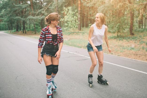 Duas mulheres jovens esbeltas e sexy e patins. uma fêmea tem patins em linha e a outra um quad. garotas cavalgam nos raios do sol.