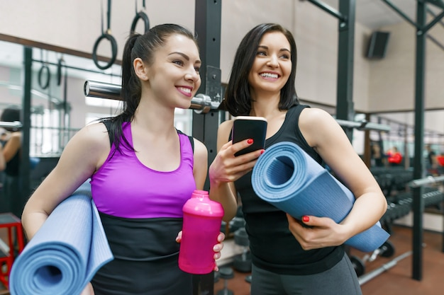 Duas mulheres jovens esportes no ginásio falando sorrindo com esteiras de fitness
