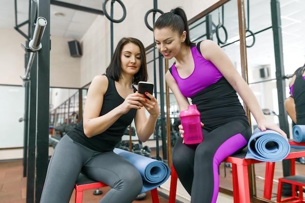 Duas mulheres jovens esportes no ginásio falando sorrindo