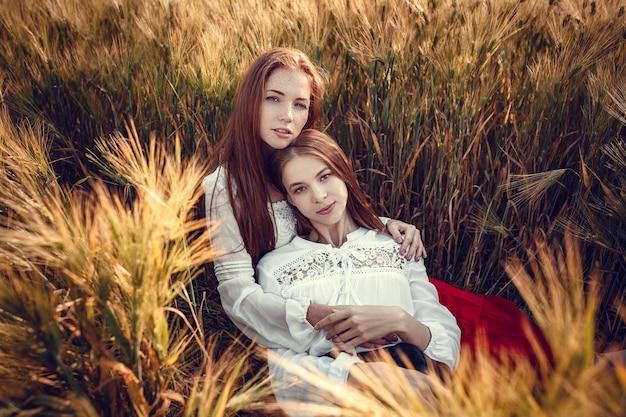 Duas mulheres jovens estão ansiosas para o pôr do sol. melhores amigos. duas jovens ruivas em um campo de trigo