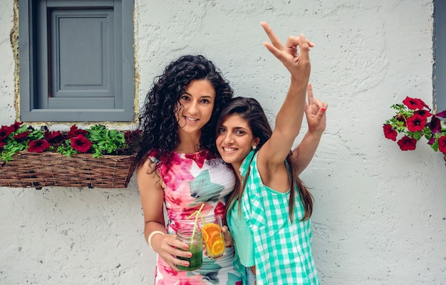 Duas mulheres jovens felizes olhando para a câmera fazendo o sinal da vitória, segurando bebidas saudáveis no fundo da parede