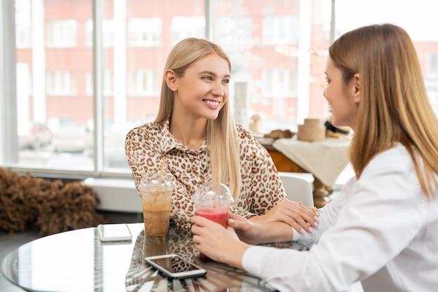 Duas mulheres jovens felizes olhando uma para a outra durante uma conversa enquanto relaxam com um copo de smoothie ou um coquetel no café