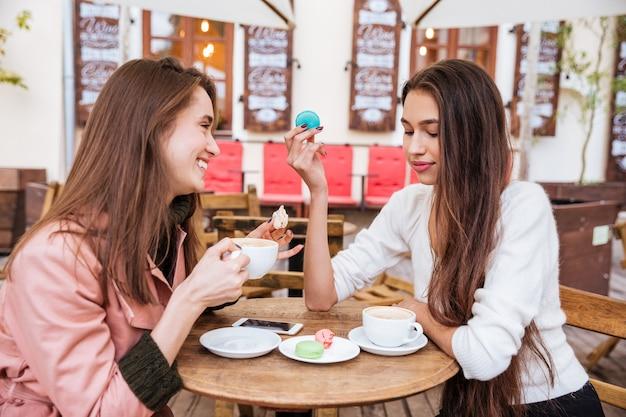 Duas mulheres jovens fofas felizes bebendo café e comendo macaroons franceses em uma cafeteria ao ar livre