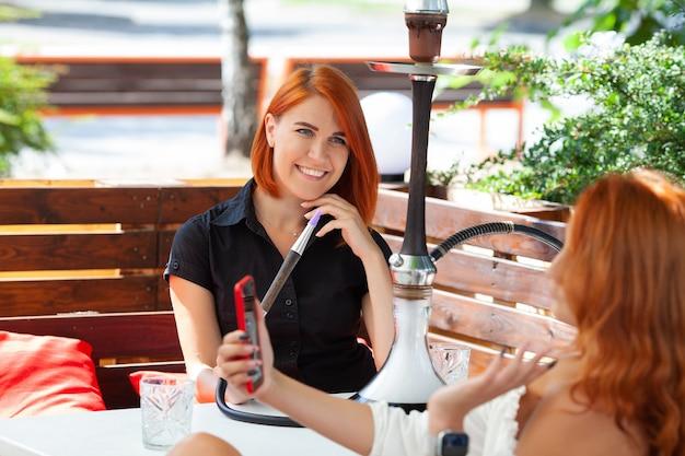 Duas mulheres jovens fumam narguilé e tomam coquetéis em um café na rua.