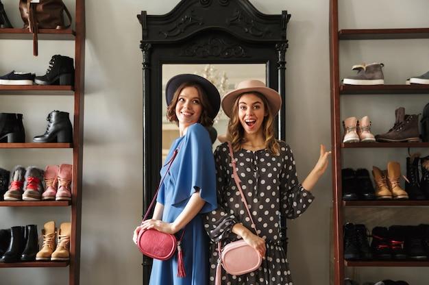 Duas mulheres jovens incríveis emocionais usando chapéus mostrando sapatos.