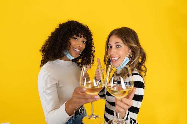 Duas mulheres jovens isoladas em um fundo amarelo, fazendo sinal de polegar para cima, usando máscara de proteção, segurando um copo de vinho branco