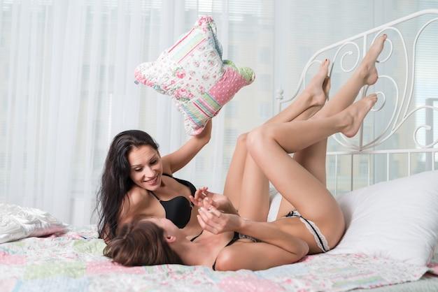 Duas mulheres jovens magras em lingerie sexy fazendo guerra de travesseiros na cama