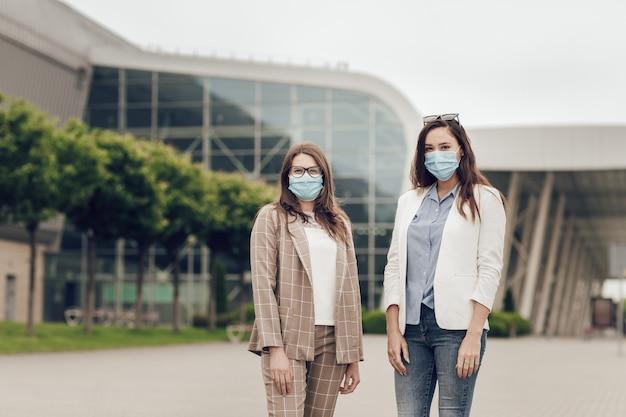 Duas mulheres jovens no fundo de um prédio ao ar livre, com máscaras médicas no rosto