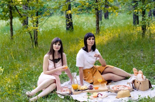 Duas mulheres jovens no parque lá fora em dia de sol. cenário de piquenique na grama com pizza, pão, suco de laranja, queijo e frutas