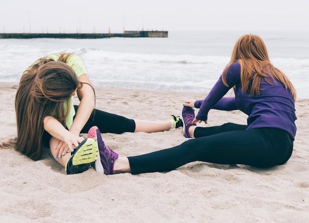 Duas mulheres jovens no sportswear fazendo alongamento na praia
