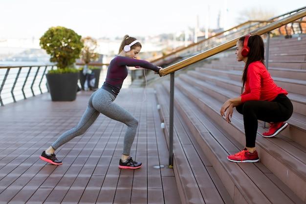 Duas mulheres jovens praticam alongamento ao ar livre