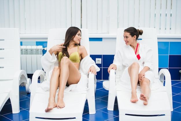 Duas mulheres jovens relaxantes à beira da piscina vestindo roupões de banho