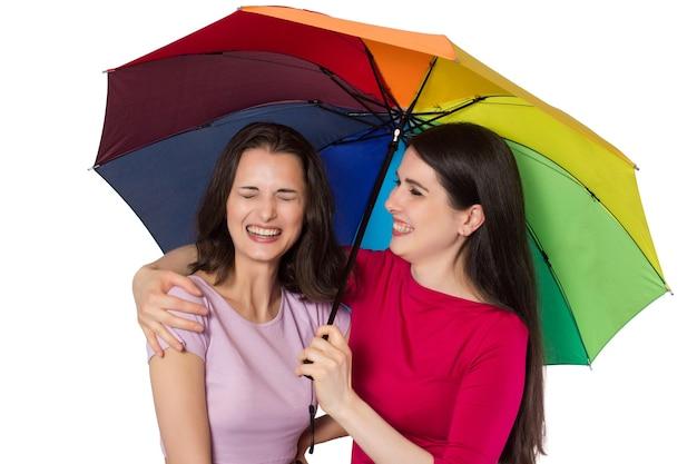 Duas mulheres jovens rindo com guarda-chuva de arco-íris.