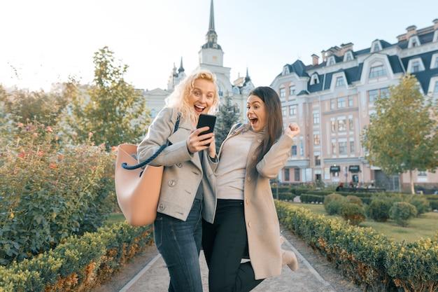 Duas mulheres jovens se divertindo, olhando para o smartphone rindo
