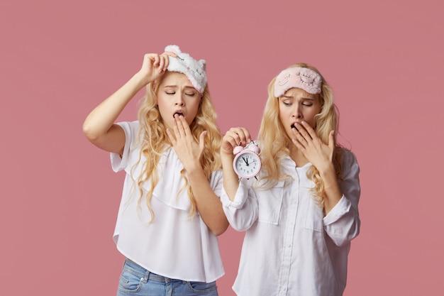 Duas mulheres jovens sem dormir gêmeas de pijama e máscaras de dormir em uma parede rosa. despertador acordou a mulher