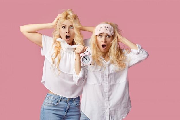 Duas mulheres jovens sem dormir gêmeas de pijama e máscaras de dormir em uma parede rosa. despertador acordou as meninas