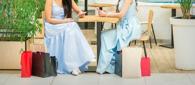Duas mulheres jovens sentadas à mesa com smartphones e sacolas de compras em um café ao ar livre