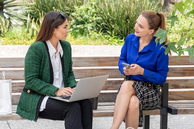 Duas mulheres jovens sentadas em um banco de rua, trabalhando em seu laptop, apontando para a tela
