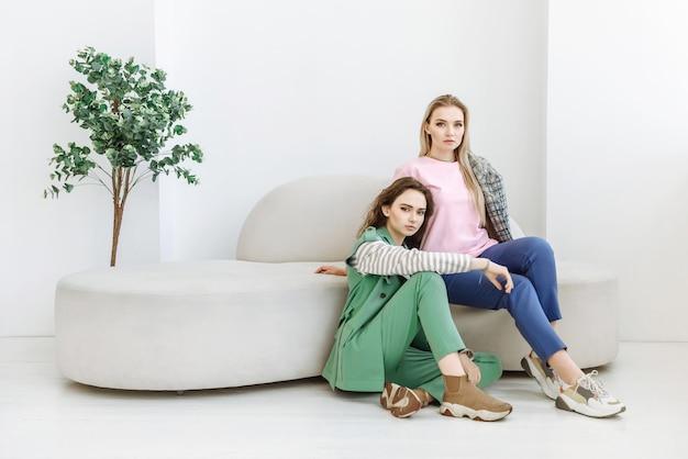 Duas mulheres jovens sentadas no sofá no interior