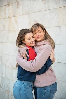 Duas mulheres jovens sorridente abraçando