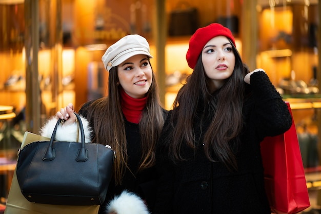 Duas mulheres jovens sorridentes atraentes estão comprando na cidade