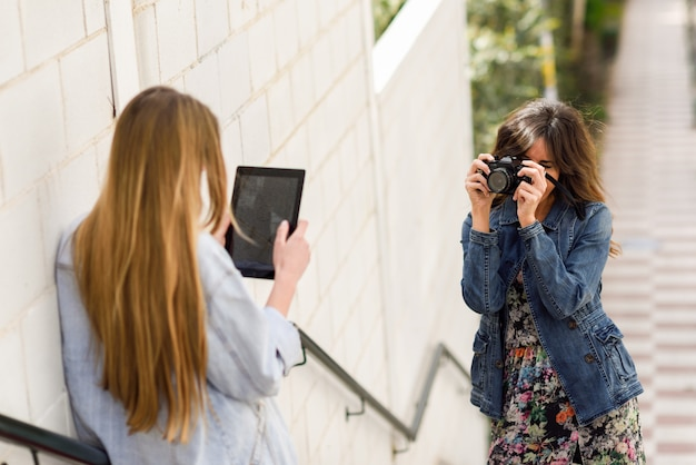 Duas mulheres jovens turistas tomando photoswith digital tablet e câmera reflex analógica