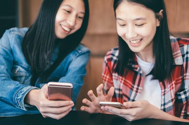 Duas mulheres jovens usando telefones celulares.