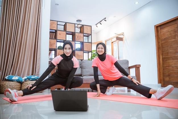 Duas mulheres jovens vestindo roupas de ginástica hijab sorriem para a câmera ao se agachar e se alongar com uma perna puxada para o lado na frente de um laptop na casa