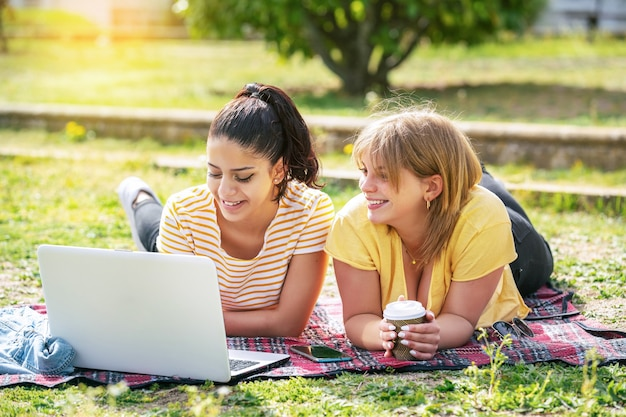Duas mulheres latinas deitadas no parque, olhando para o computador e tomando café em um dia ensolarado