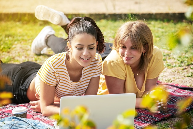 Duas mulheres latinas deitadas no parque olhando para o computador em um dia ensolarado