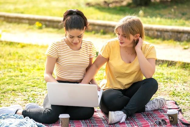 Duas mulheres latinas sentadas no parque olhando para o computador em um dia ensolarado