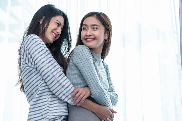 Duas mulheres lésbicas asiáticas abraçar e abraçar juntos no quarto