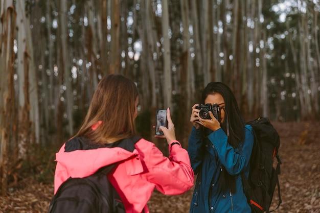 Duas mulheres, levando, fotografia, de, um ao outro, com, câmera, e, cellphone