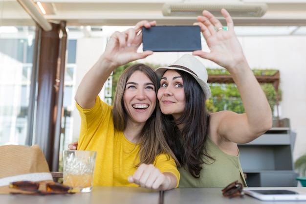 Duas mulheres lindas tomando café da manhã em um restaurante e tomar uma selfie com telefone móvel. eles estão rindo. estilo de vida dentro e conceito de amizade