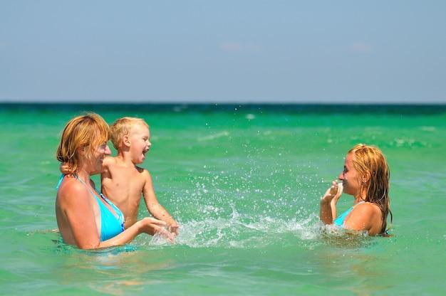 Duas mulheres loiras e um garotinho em pé, curtindo a água em um dia ensolarado de verão
