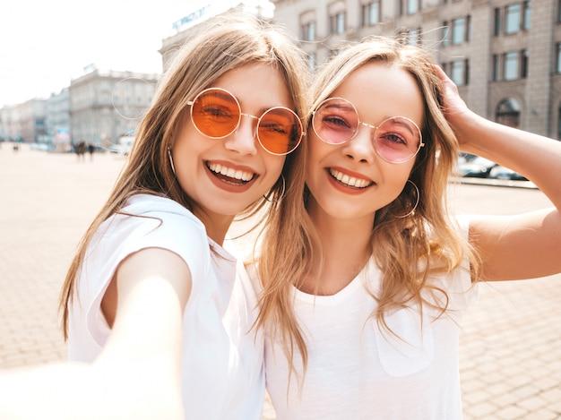 Duas mulheres loiras hipster sorridente jovens em roupas de camiseta branca de verão.