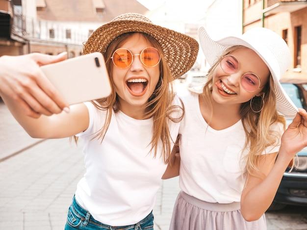Duas mulheres loiras hipster sorridente jovens em t-shirt branca de verão. meninas tirando fotos de auto-retrato de selfie em smartphone. modelos posando na rua fundo. feminino mostra a língua e as emoções positivas