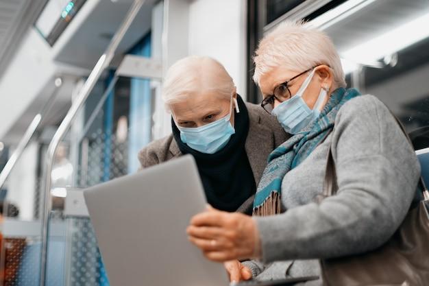 Duas mulheres maduras usando um laptop enquanto estão sentadas em um vagão do metrô