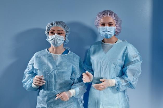 Duas mulheres médicas cirurgiões em pé antes da cirurgia e olhando para a câmera na superfície azul