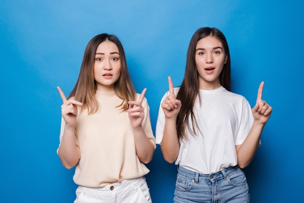 Duas mulheres mestiças espantadas apontam com o dedo indicador para cima, têm expressões felizes, isoladas na parede azul.