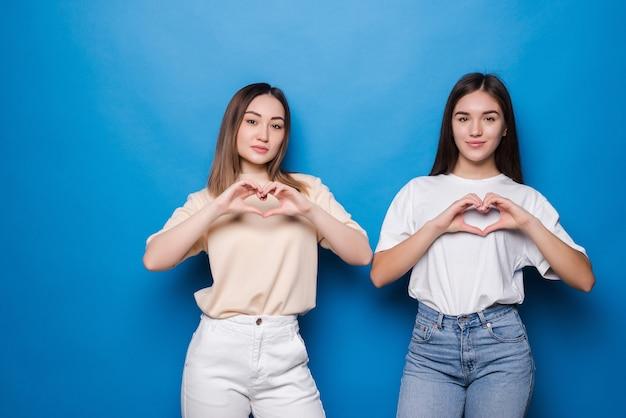 Duas mulheres mestiças fazendo coração na parede azul