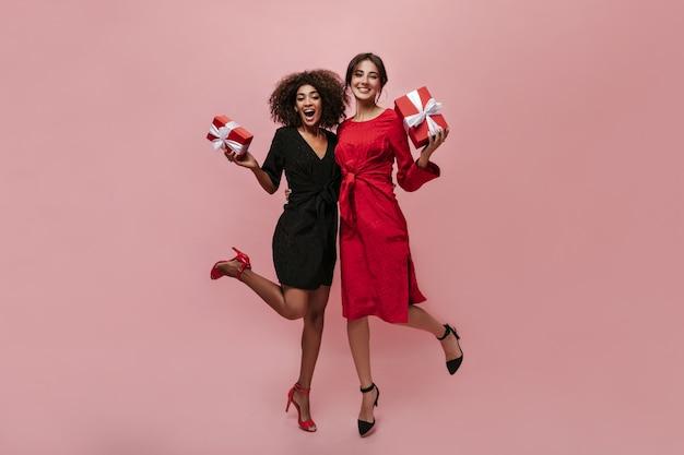 Duas mulheres modernas emocionantes com um penteado escuro da moda em roupas elegantes de bolinhas e sapatos vermelhos e pretos abraçando e segurando caixas de presente vermelhas
