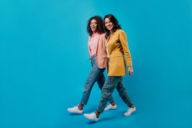 Duas mulheres morenas caminhando pelo estúdio