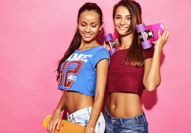 Duas mulheres morenos sorridentes elegantes jovens com skates centavo. modelos em roupas de esporte hipster de verão posando perto de parede rosa. fêmea positiva